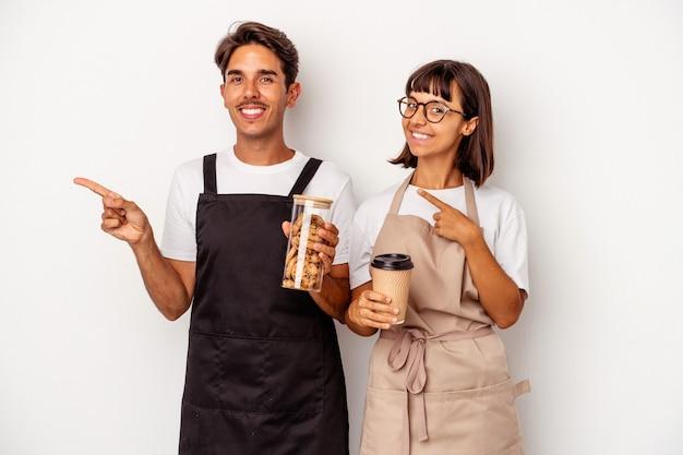 Jong gemengd ras winkelbediende paar geïsoleerd op een witte achtergrond glimlachend en opzij wijzend, iets tonen op lege ruimte.