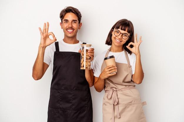 Jong gemengd ras winkelbediende paar geïsoleerd op een witte achtergrond vrolijk en zelfverzekerd weergegeven: ok gebaar.