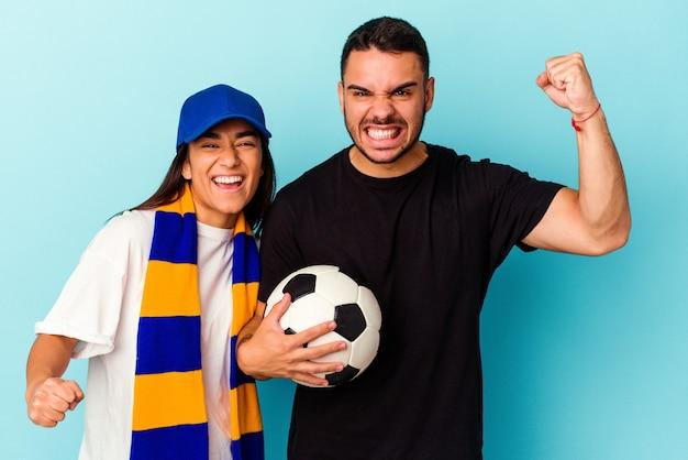 Jong gemengd raspaar dat huis schoonmaakt dat op blauwe achtergrond wordt geïsoleerd en vuist opheft na een overwinning, winnaarconcept.