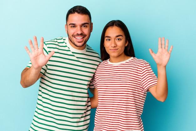 Jong gemengd raspaar dat op blauwe achtergrond wordt geïsoleerd die vrolijk glimlacht die nummer vijf met vingers toont.