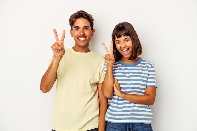 Jong gemengd raspaar dat op witte achtergrond wordt geïsoleerd die nummer twee met vingers toont.