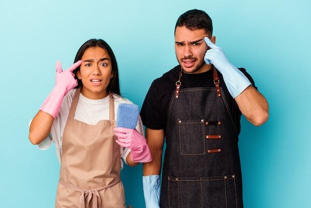 Jong gemengd raspaar die huis schoonmaken dat op blauwe achtergrond wordt geïsoleerd die een teleurstellinggebaar met wijsvinger toont.