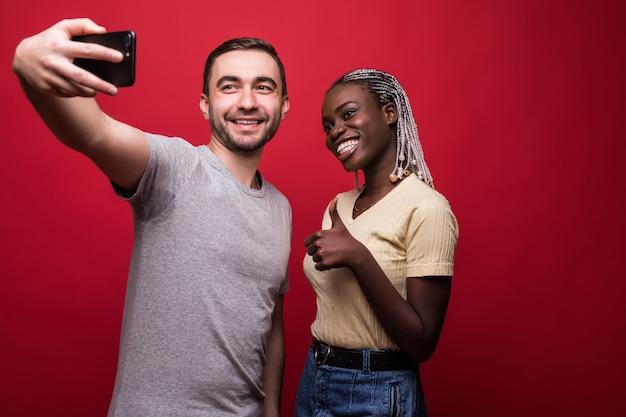 Jong gemengd raspaar, kaukasische man en afrikaanse vrouw die selfie van telefoon nemen terwijl status op rode achtergrond