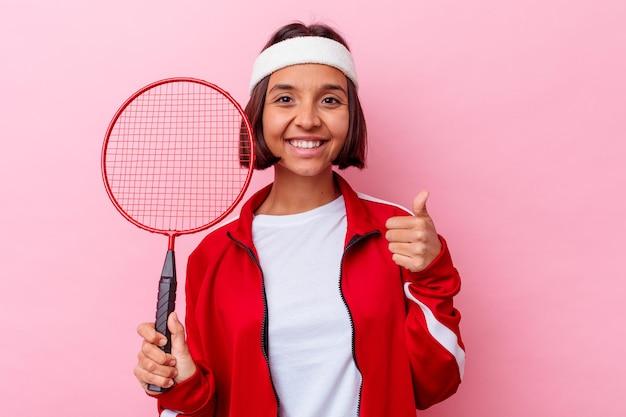 Jong gemengd rasvrouw die badminton spelen dat op roze muur glimlacht en duim opheft
