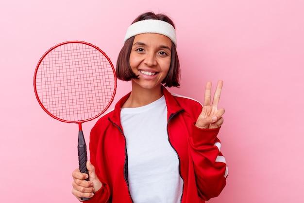 Jong gemengd rasvrouw die badminton spelen dat op roze muur wordt geïsoleerd die nummer twee met vingers toont.