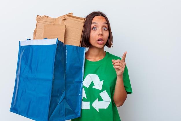 Jong gemengd rasvrouw recyclingskarton dat op witte muur wordt geïsoleerd die een idee, inspiratieconcept heeft.