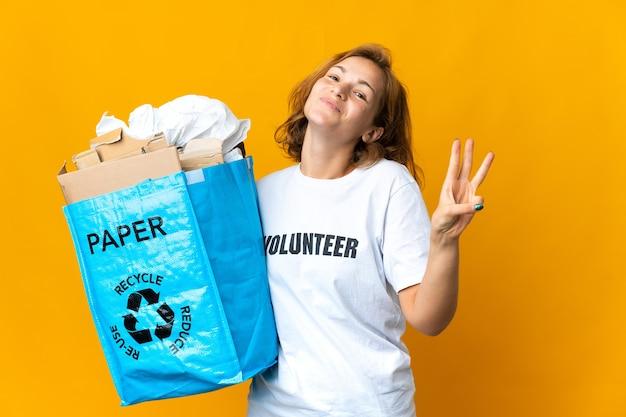 Jong georgisch meisje dat een recyclingzak vol papier houdt om gelukkig te recyclen en drie met vingers telt