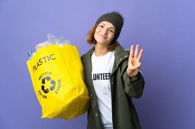 Jong georgisch meisje dat een zak vol plastic flessen houdt om gelukkig te recyclen en drie met vingers te tellen
