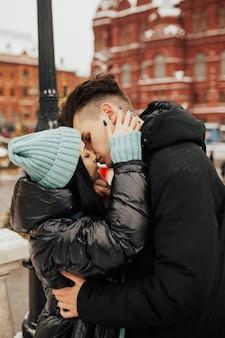 Jong gepassioneerd paar zachtjes kussen op kerst straat