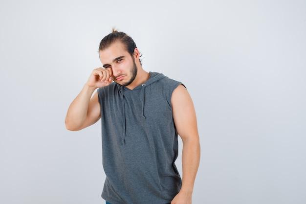 Jong geschikt mannetje dat zijn oog in mouwloos vest wrijft en boos, vooraanzicht kijkt.