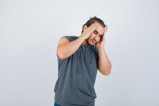 Jong geschikt mannetje in mouwloze hoodie die aan hoofdpijn lijdt en er onwel uitziet, vooraanzicht.