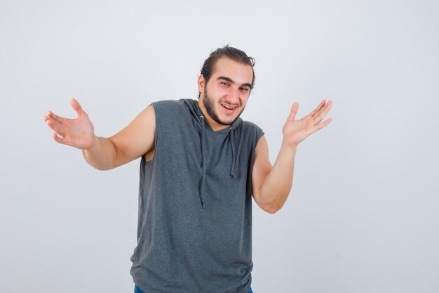 Jong geschikt mannetje in mouwloze hoodie die grootteteken toont en vrolijk, vooraanzicht kijkt.