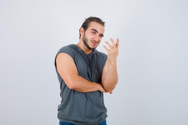 Jong geschikt mannetje in mouwloze hoodie die op vragende wijze de hand opheft en er vrolijk uitziet, vooraanzicht.