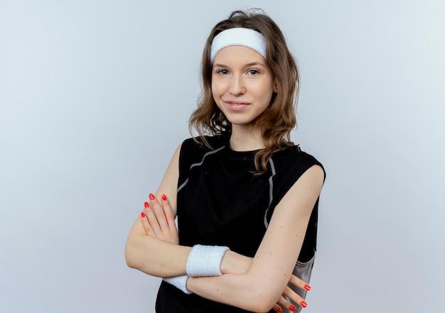 Jong geschiktheidsmeisje die in zwarte sportkleding met gekruiste wapens glimlachen die zich over witte muur bevinden