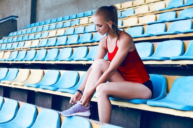 Jong geschiktheidsmeisje die tennisschoenen dragen die voor looppas voorbereidingen treffen