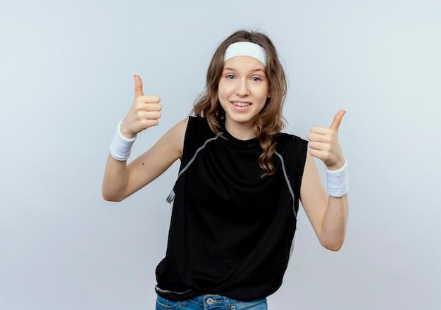 Jong geschiktheidsmeisje in zwarte sportkleding die met hoofdband glimlachen tonen duimen die omhoog zich over witte muur bevinden