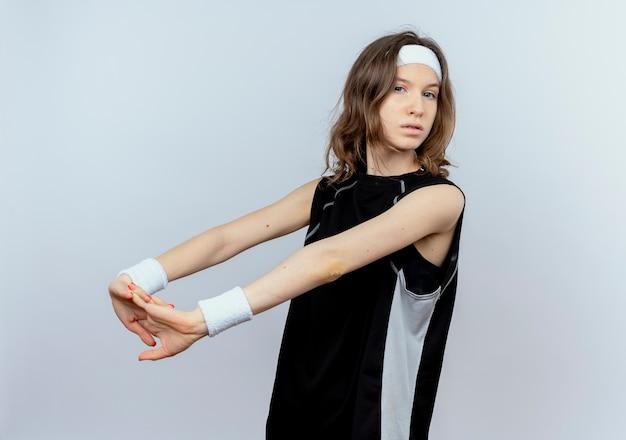 Jong geschiktheidsmeisje in zwarte sportkleding die met hoofdband haar handen sretching die zich zelfverzekerd over witte muur bevinden