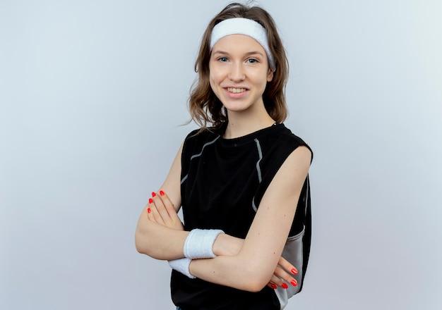 Jong geschiktheidsmeisje in zwarte sportkleding die met hoofdband met gekruiste handen glimlachen die zich over witte muur bevinden