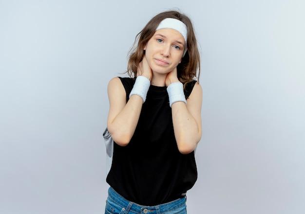Jong geschiktheidsmeisje in zwarte sportkleding die met hoofdband onwel kijkt aanrakende nek met pijn die zich over witte muur bevindt