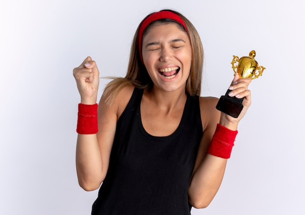 Jong geschiktheidsmeisje in zwarte sportkleding en rode hoofdband die trofee balde vuist blij en opgewonden status over witte muur
