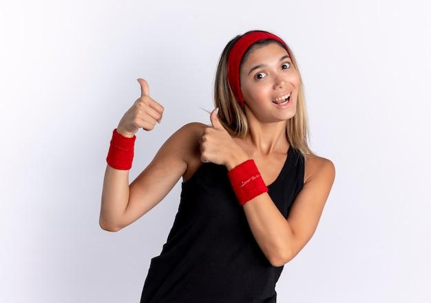 Jong geschiktheidsmeisje in zwarte sportkleding en rode hoofdband lookign glimlachend tonen duimen omhoog die zich over witte muur bevinden