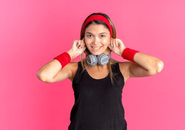 Jong geschiktheidsmeisje in zwarte sportkleding en rode hoofdband met hoofdtelefoons die pret glimlachen die zich over roze muur bevinden