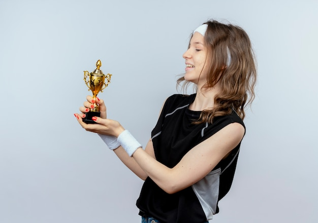 Jong geschiktheidsmeisje in zwarte sportkleding met de trofee die van de hoofdbandholding het tevreden en gelukkig status over witte muur bekijken