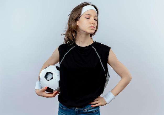Jong geschiktheidsmeisje in zwarte sportkleding met het voetbal die van de hoofdbandholding opzij zekere status over witte muur kijken