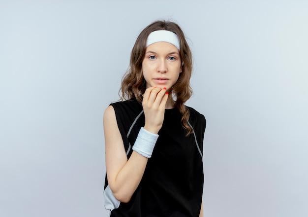Jong geschiktheidsmeisje in zwarte sportkleding met hoofdband beklemtoond en zenuwachtig status over witte muur