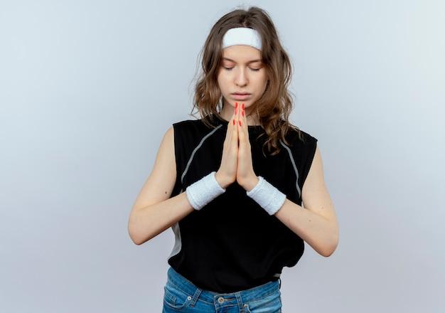 Jong geschiktheidsmeisje in zwarte sportkleding met hoofdband die palmen bij elkaar houden zoals bidden met hoopuitdrukking die zich over witte muur bevindt