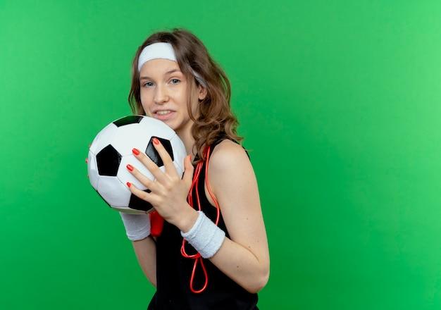 Jong geschiktheidsmeisje in zwarte sportkleding met hoofdband en springtouw rond hals die voetbal die status over groene muur glimlachen houden