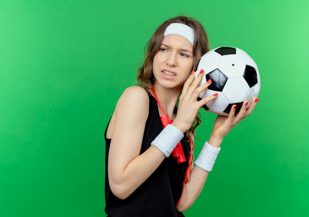 Jong geschiktheidsmeisje in zwarte sportkleding met hoofdband en springtouw rond hals die voetbal houdt die ontevreden over groene muur kijkt