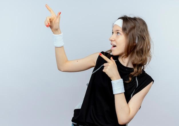 Jong geschiktheidsmeisje in zwarte sportkleding met hoofdband glimlachend wijzend met vingers aan de kant die zich over witte muur bevinden