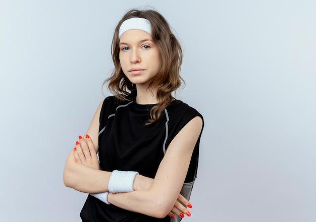 Jong geschiktheidsmeisje in zwarte sportkleding met hoofdband met ernstig gezicht met gekruiste wapens die zich over witte muur bevinden