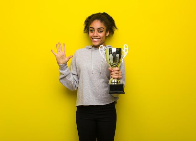 Jong geschiktheidszwart vrouw die nummer vijf tonen. een trofee houden.