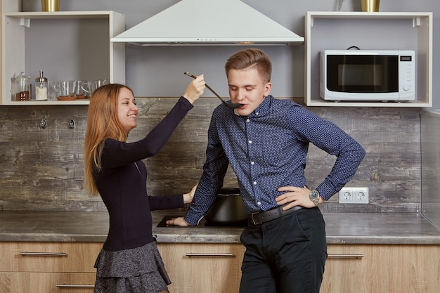 Jong getrouwd stel in de keuken in hun appartement.