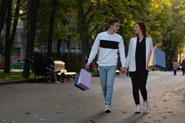 Jong getrouwd stel loopt na het winkelen in het park met aankopen in hun handen. gelukkige minnaars.