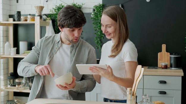 Jong getrouwd stel maakt gebruik van een digitale tablet en glimlacht tijdens het koken in de keuken thuis