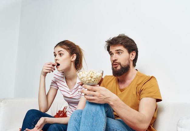 Jong getrouwd stel ontspannen thuis op de bank popcorn entertainment