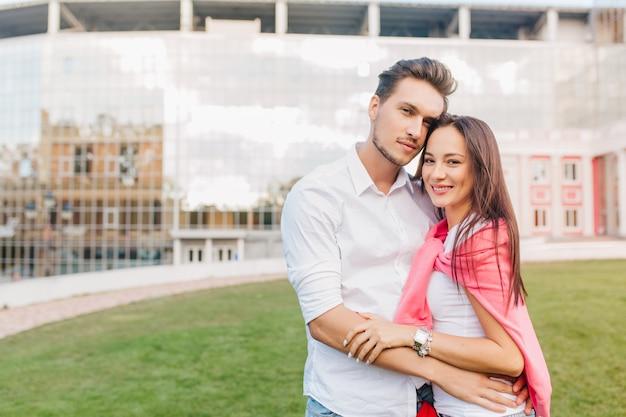 Jong getrouwd stel poseren samen voor modern gebouw tijdens gezamenlijk weekend