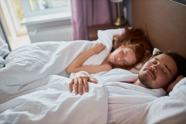 Jong getrouwd stel slapen samen, liggen 's ochtends op bed