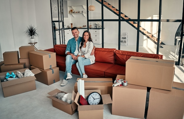 Jong getrouwd stel zittend op de bank in de woonkamer thuis. glimlachende gelukkige vrouw en man ontspannen rustende ongeopende bezittingen nog steeds in hun kartonnen dozen. verhuizen en verhuizen nieuw huis concept.