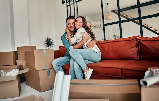 Jong getrouwd stel zittend op een bank knuffelen in de woonkamer thuis. gelukkige man en vrouw hebben plezier, kijken uit naar een nieuw huis. verhuizen, een huis kopen, appartement concept.