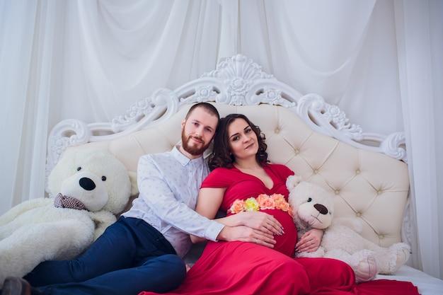 Jong gezin bereidt zich voor om ouders te worden. man knuffelt zachtjes zijn zwangere vrouw thuis op de bank. concept van moederschap en vaderschap.