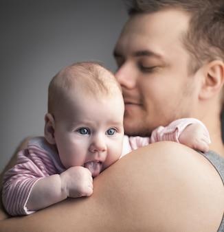 Jong gezin. de vader houdt de dochter op handen. de man niet geschoren en hij glimlacht. babymeisje met tong die uitsteekt. kleurenfoto