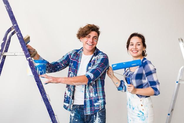 Jong gezin doet herinrichting en schilderen muren samen en lachen.