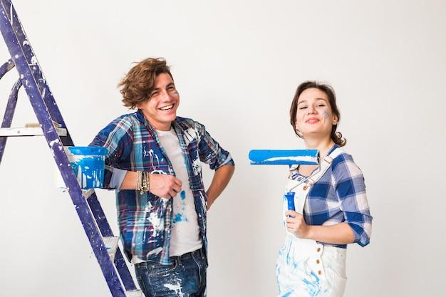 Jong gezin doet reparatie en schilderen muren samen en lachen.