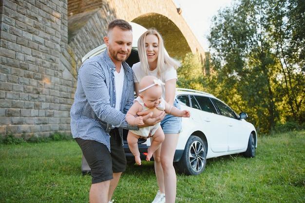 Jong gezin drie mensen in witte kleren hebben picknick. mooie ouders en dochter reizen met de auto tijdens de zomervakantie. scène in park