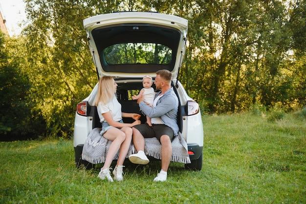 Jong gezin drie mensen in witte kleren hebben picknick. mooie ouders en dochter reizen met de auto tijdens de zomervakantie.