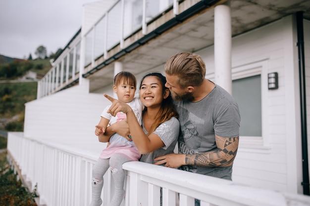 Jong gezin en kind in de verte kijkend op het huisterras